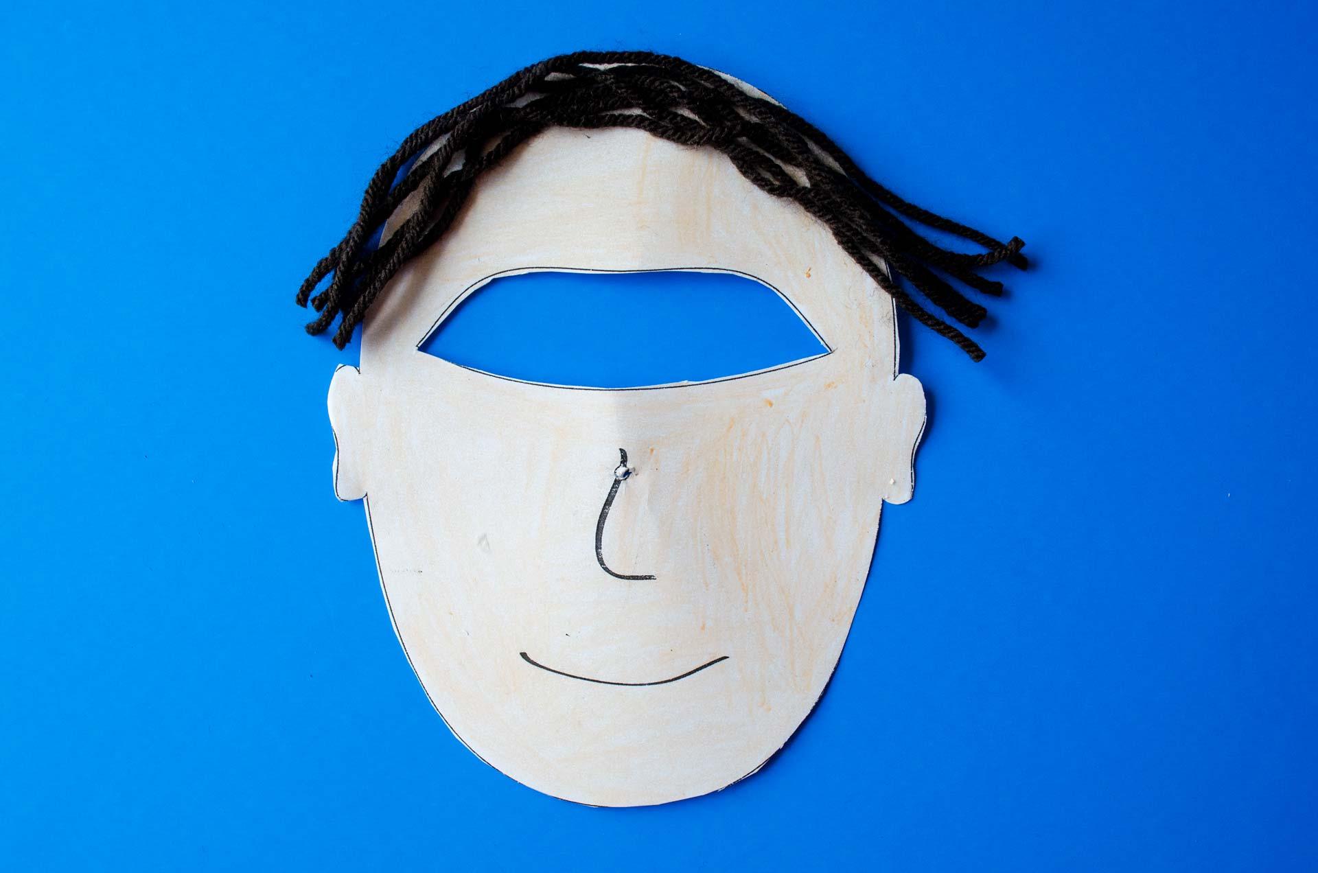 Man face illustration on blue background with black yarn hair glued on.