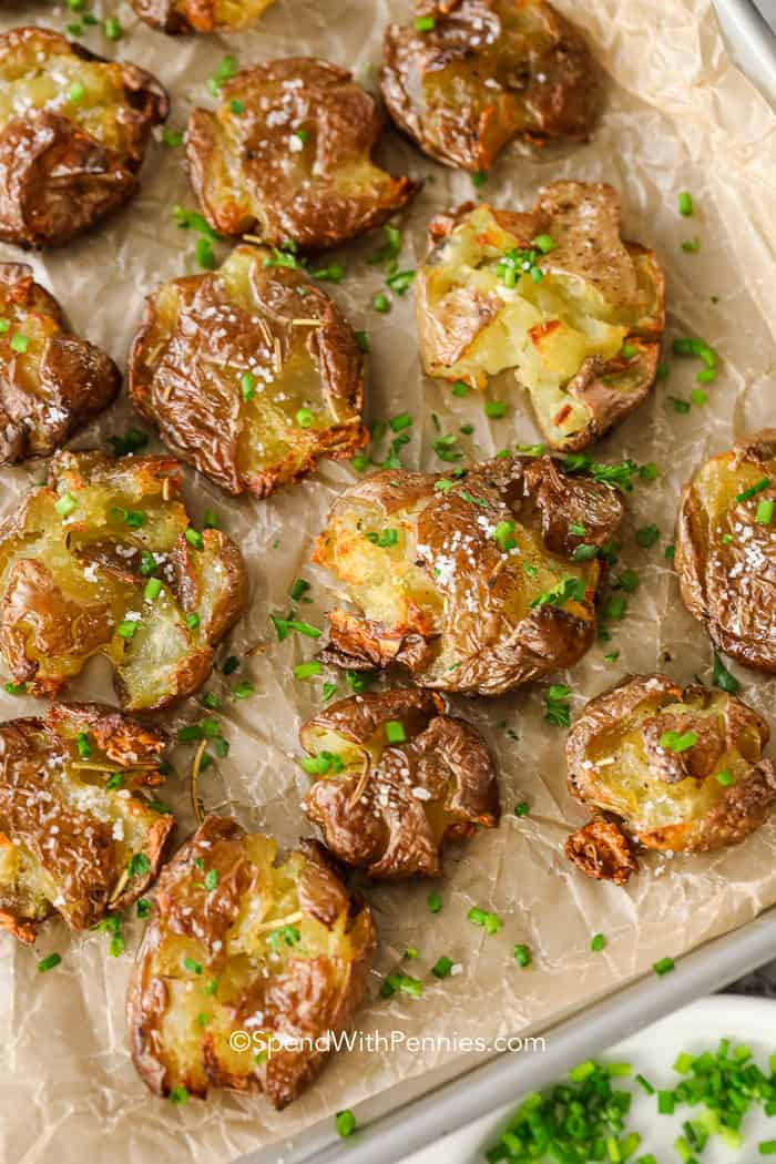 smashed baby potatoes with chopped rosemary on a brown parchment lined sheet tray