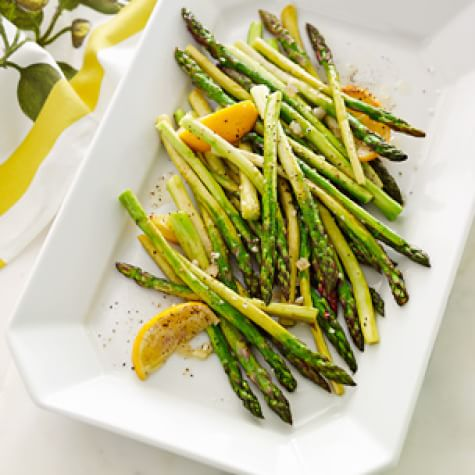 roasted asparagus on a white rectangular plate with lemon wedges for easy easter dinner