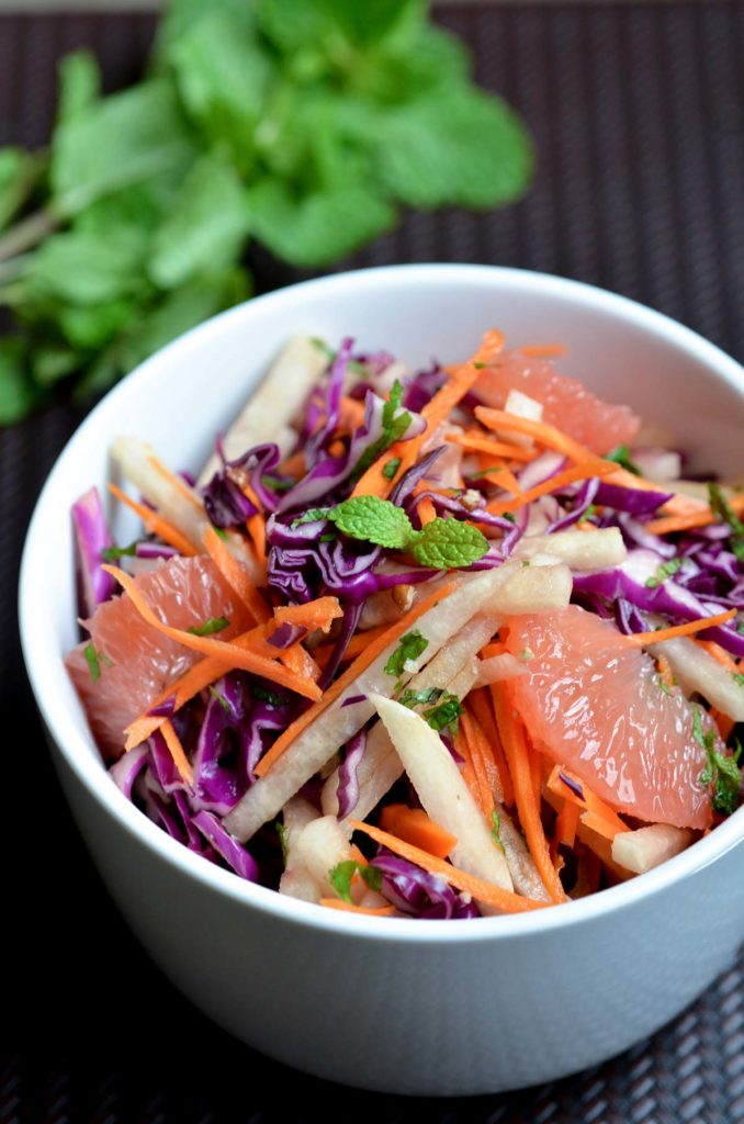 jicama, grapefruit, mint, red cabbage and pecan salad in a white bowl