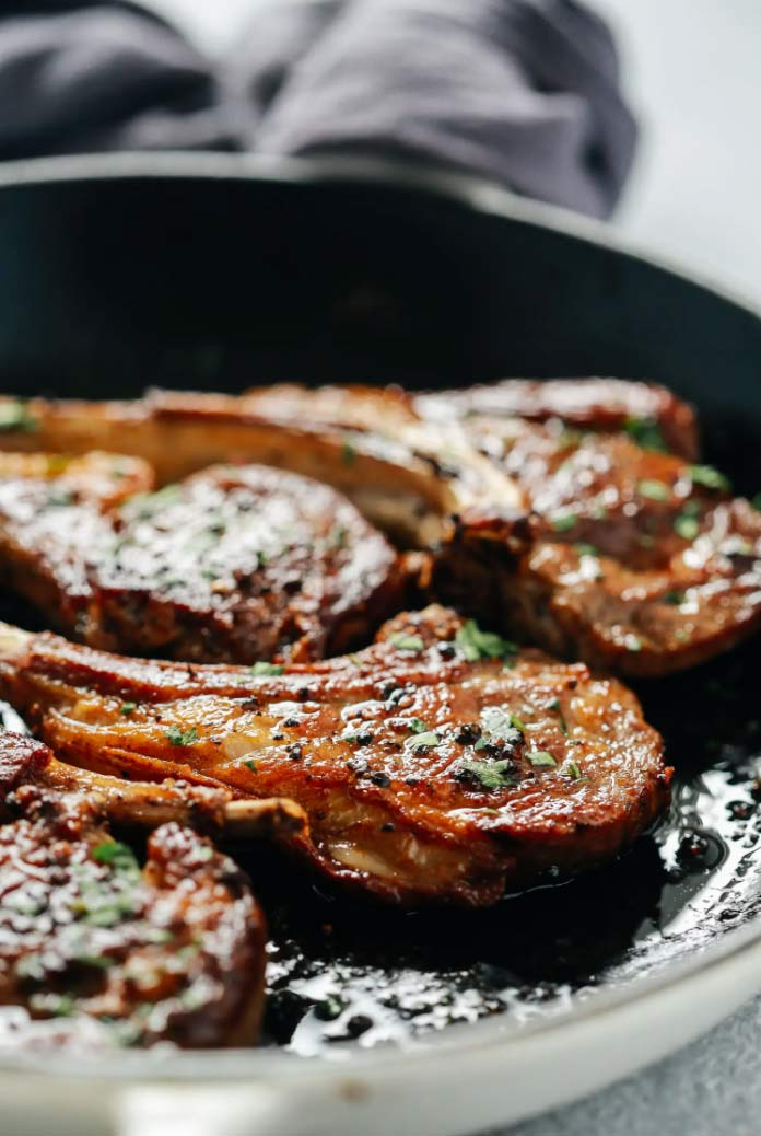 three lamb chops on a cast pan with herbs and butter for easy easter dinner