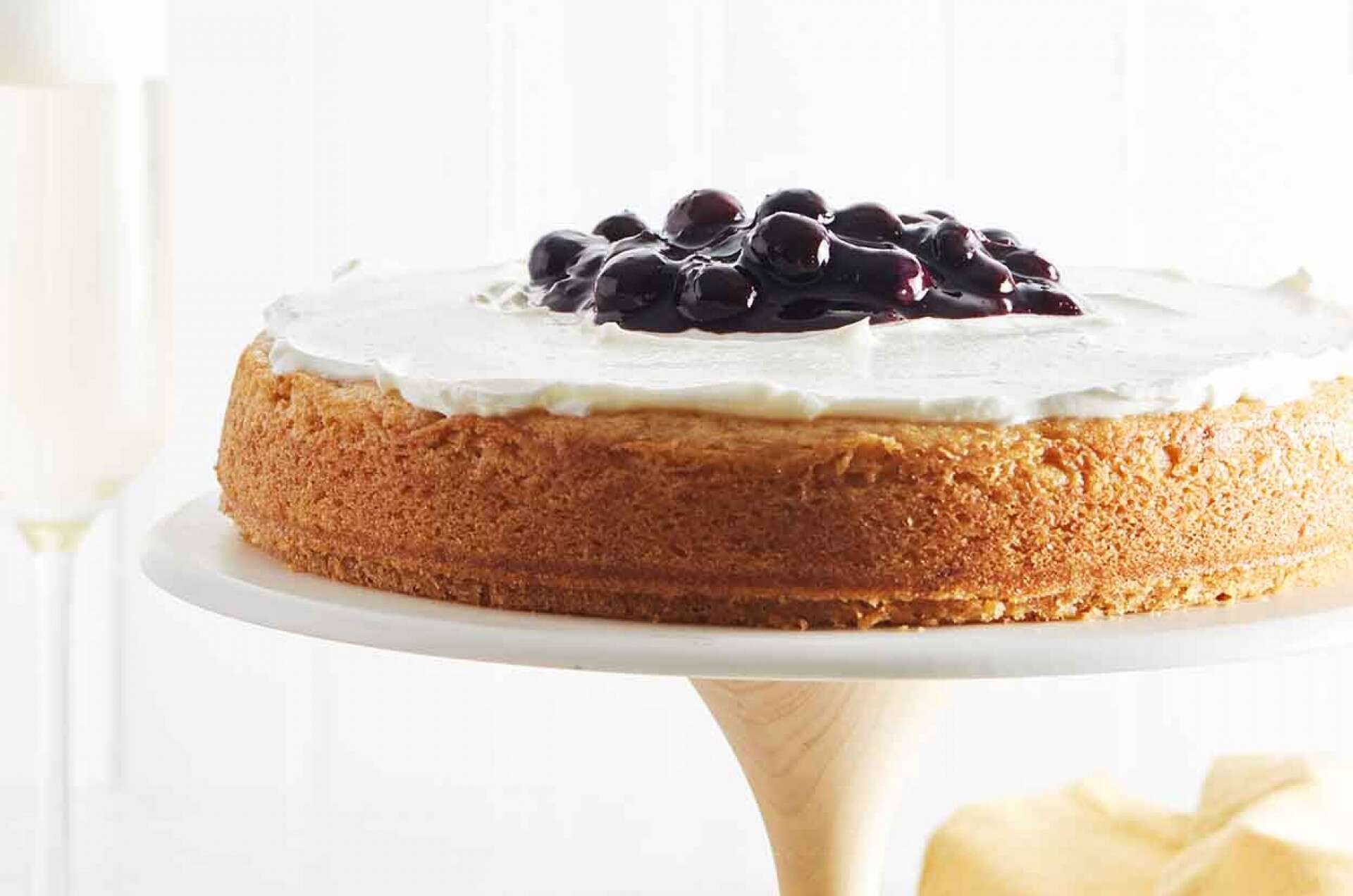 lemon cake on a white cake stand with white icing and blue berry compote
